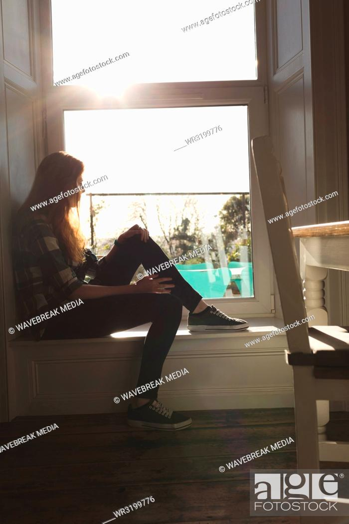 Stock Photo: Woman siting near window at home.