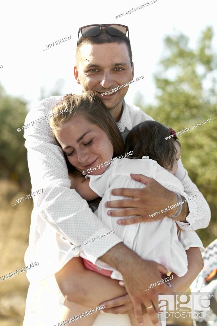 Imagen: father embracing mother and one child, enjoying togetherness, outdoors in nature. Sensible, bonding, love.