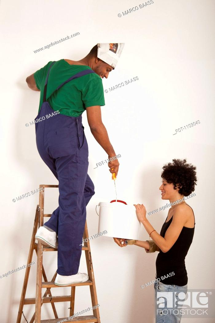 Stock Photo: A woman holding a bucket for a man painting a wall with a paint roller.