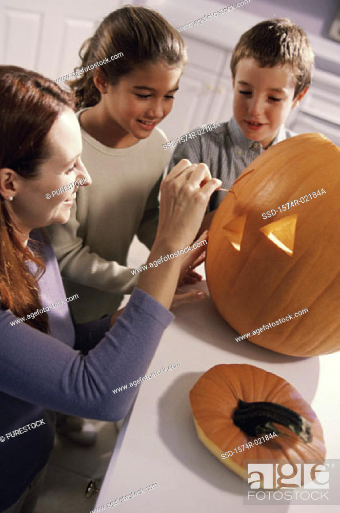 Stock Photo: Mother carving a pumpkin with her son and daughter.