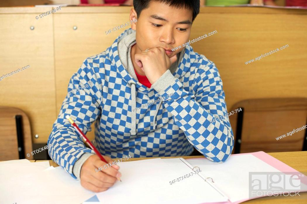 Stock Photo: Reflective student doing assignment.