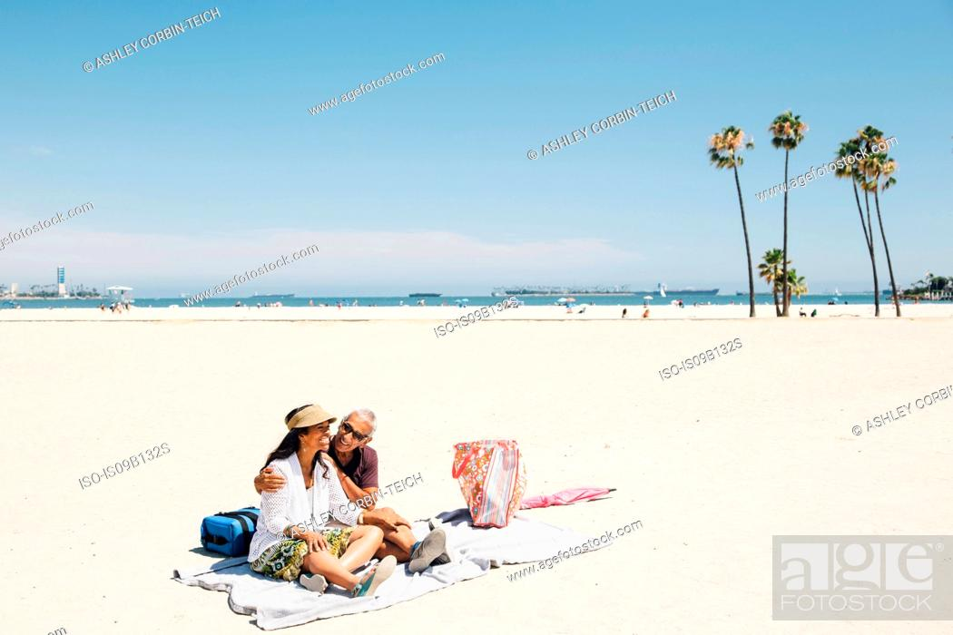 Stock Photo: Senior couple sitting on picnic blanket on beach, Long Beach, California, USA.