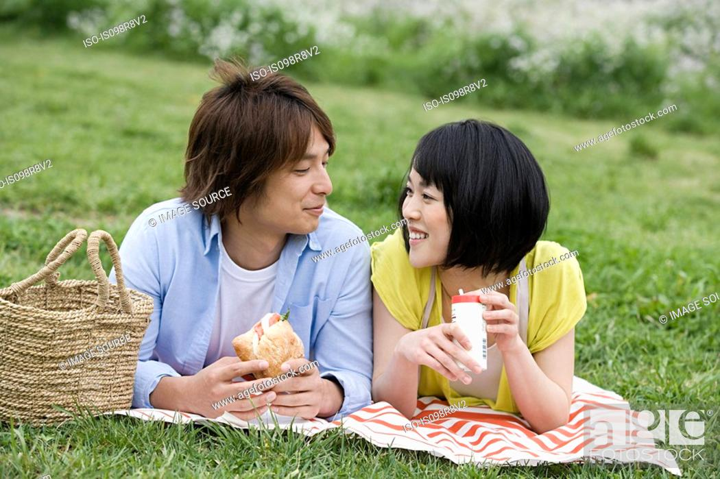 Stock Photo: Couple having lunch on the grass.