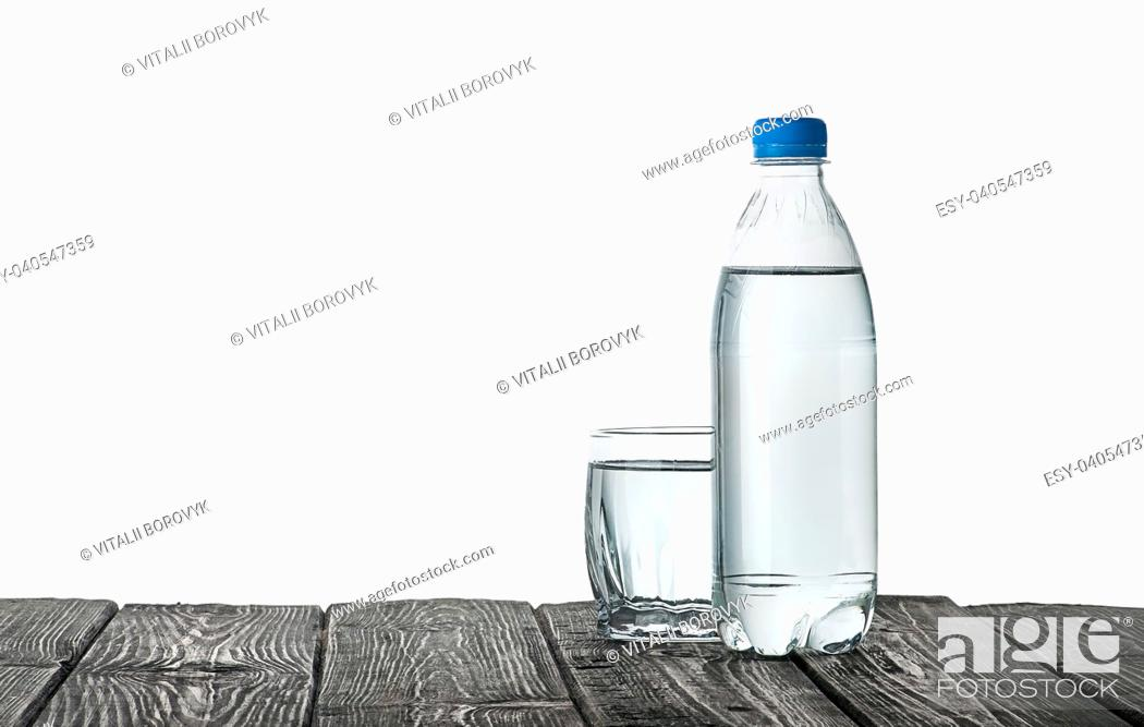 Stock Photo: Plastic bottle and a glass with water. Wooden table. Isolated on white background.
