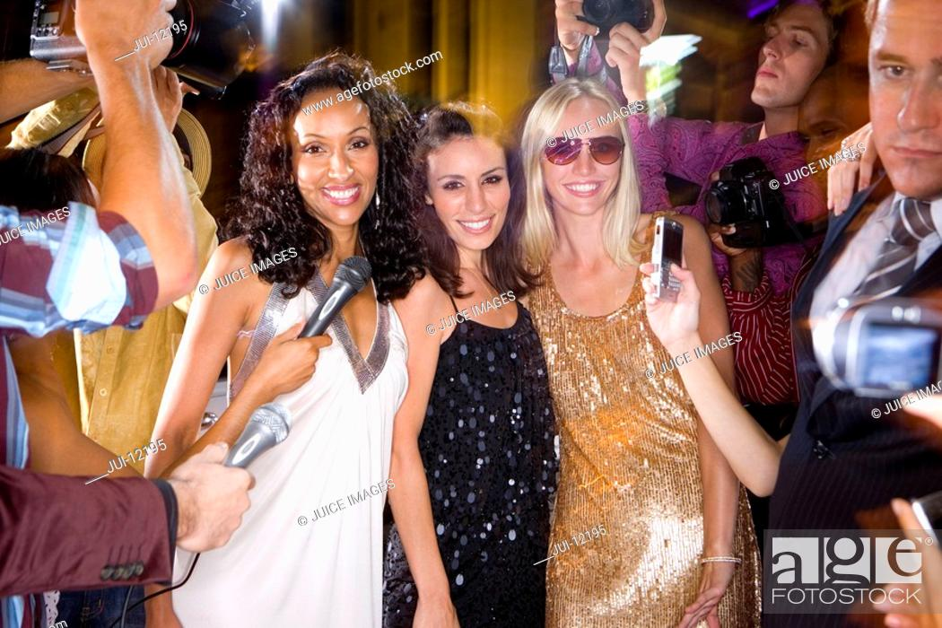 Stock Photo: Small group of young women surrounded by paparazzi, smiling, portrait.