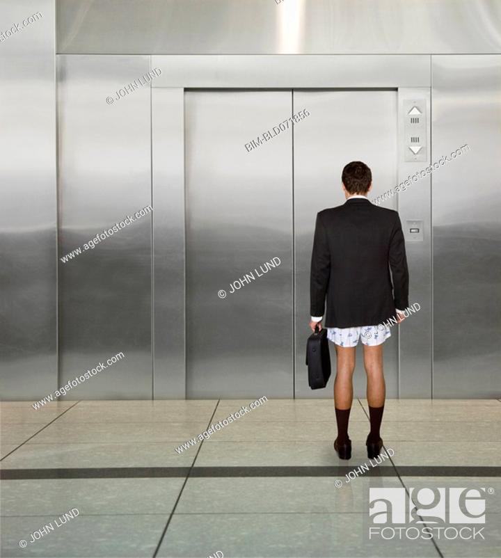 Stock Photo: Businessman not wearing pants in front of elevator.