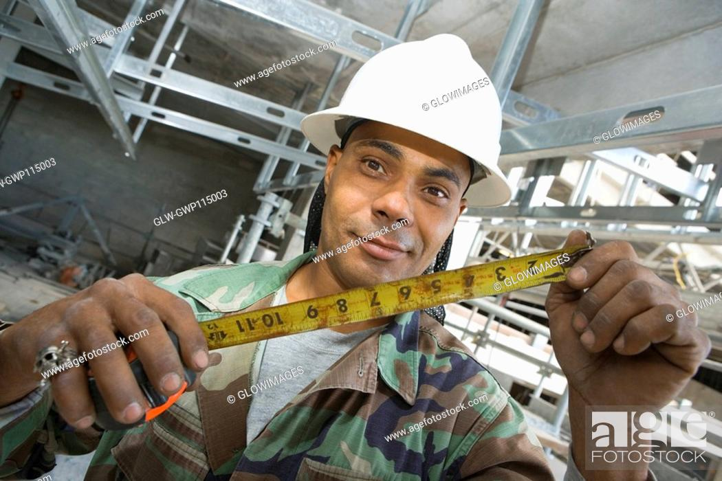 Stock Photo: Portrait of a male construction worker holding a tape measure.