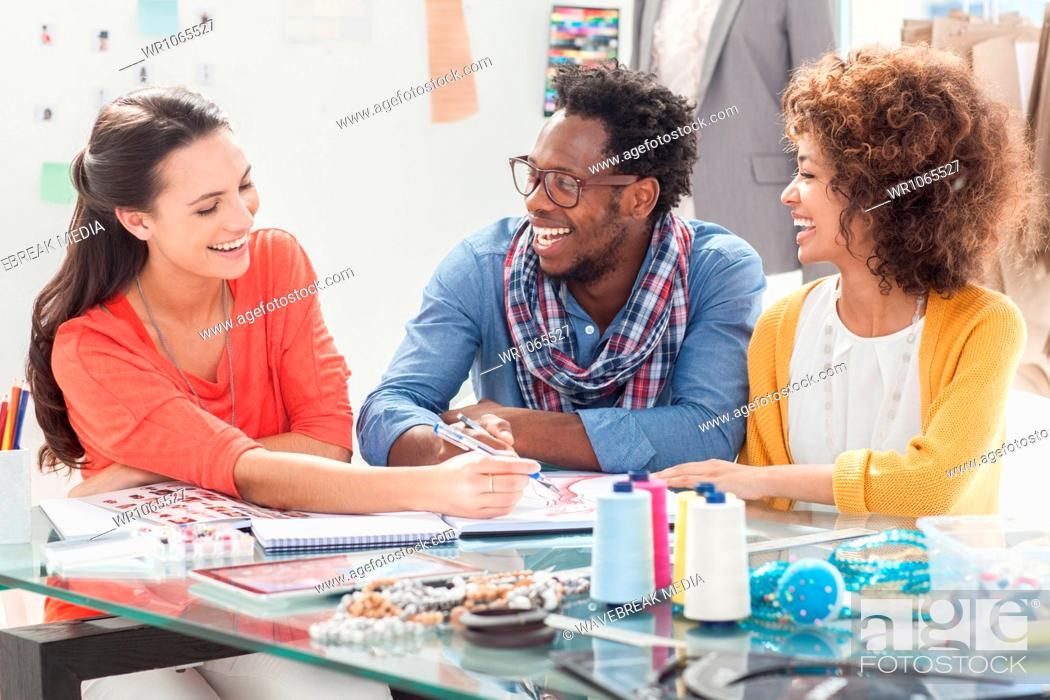 Stock Photo: Cheerful fashion designers working together.