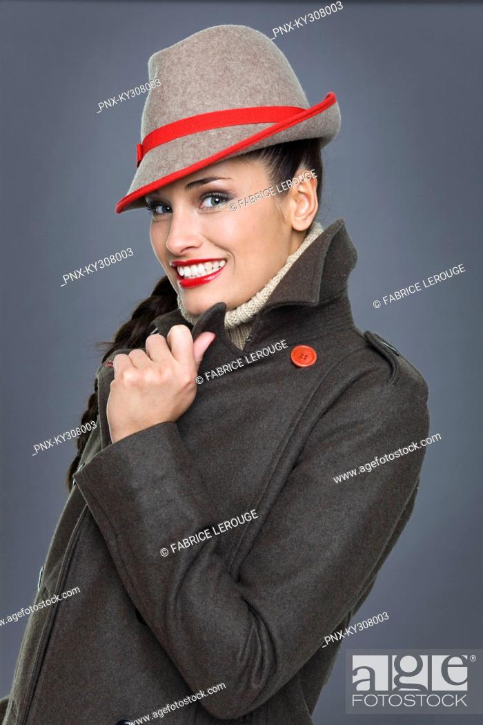 Stock Photo: Young woman wearing jacket and fedora.