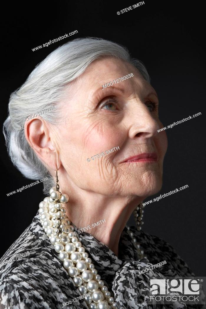 Stock Photo: Senior Woman with Pearl Earrings looking up.