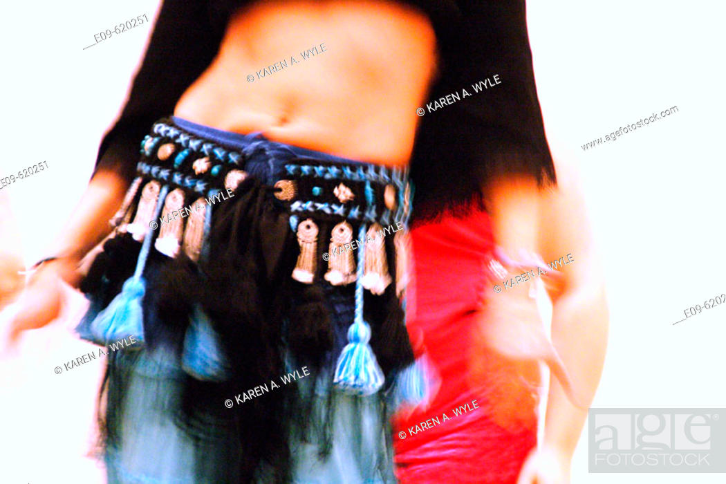 Stock Photo: torso and arms of slim belly dancer, another dancer's torso partially visible in background.