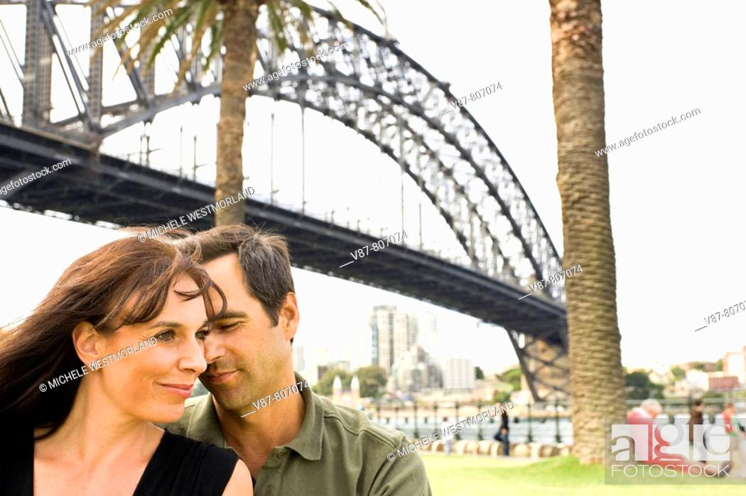 Stock Photo: couple (ages 43 and 42) sitting in park near The Rocks and Sydney Harbour Bridge. Sydney, Australia.