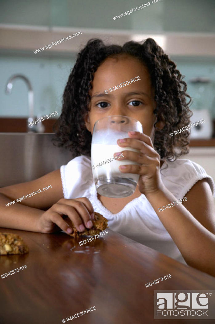 Stock Photo: Girl with milk and cookies.