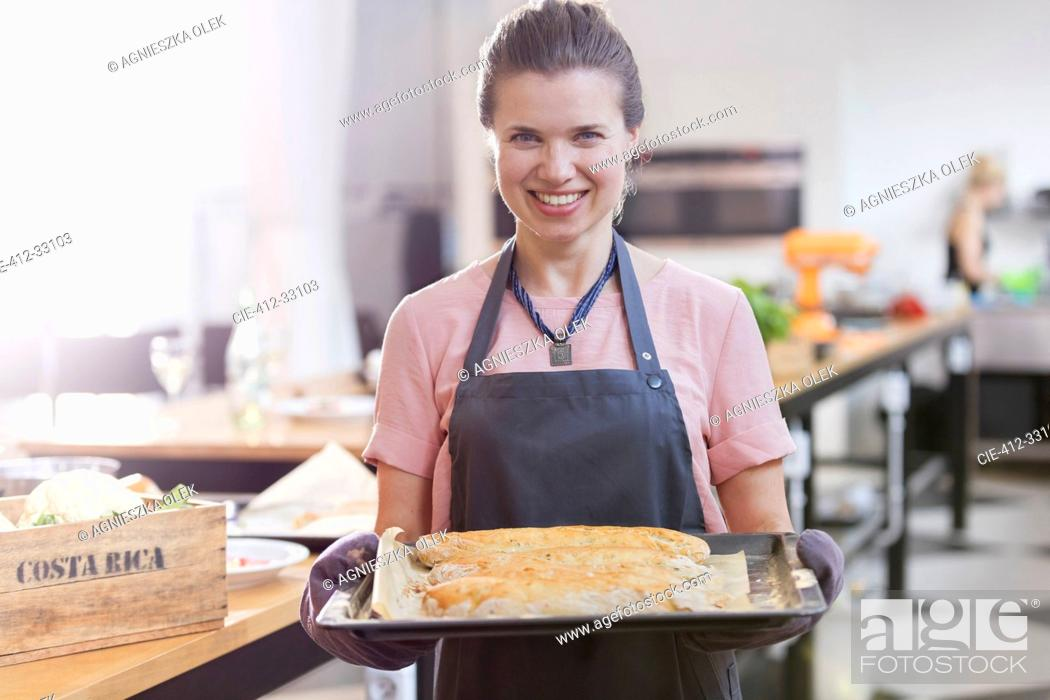 Stock Photo: Portrait smiling woman holding tray of food in cooking class kitchen.