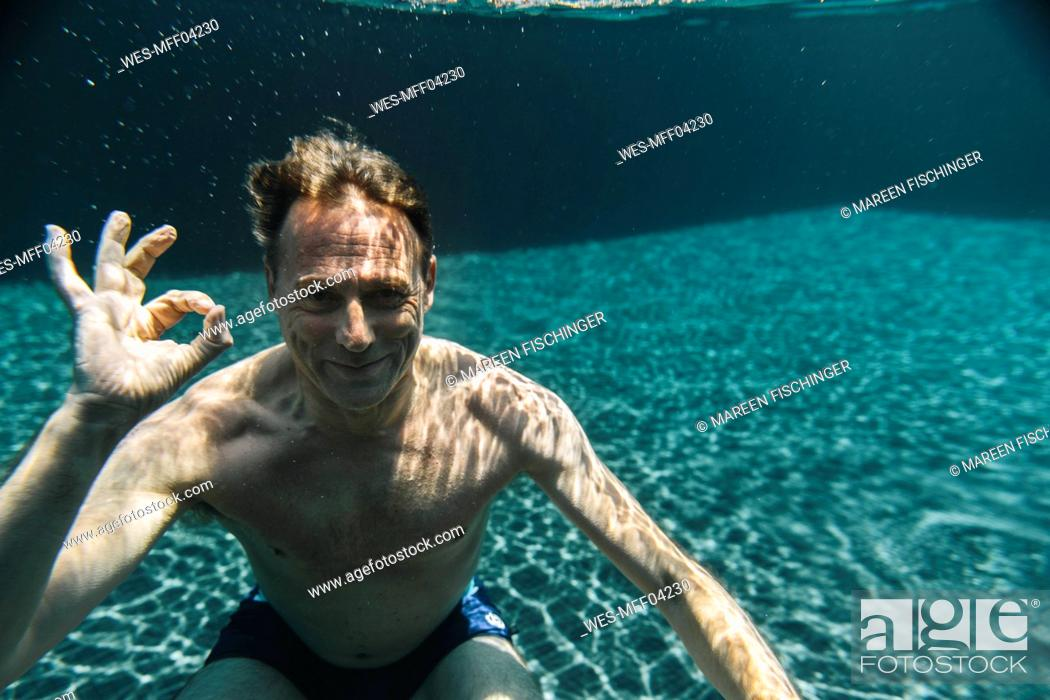 Photo de stock: Portrait of smiling man underwater in a swimming pool making ok sign.