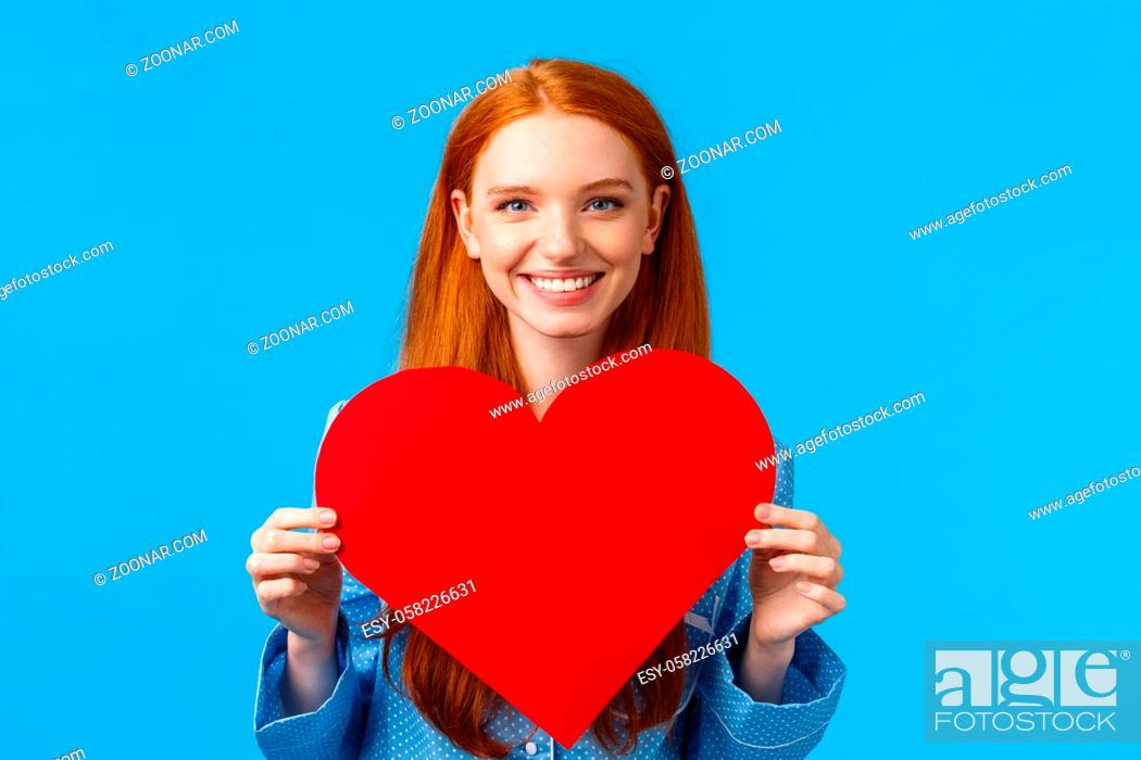 Stock Photo: Happy, cheerful and lovely, tender caucasian woman holding big red heart valentines card and smiling, giving her love and care.