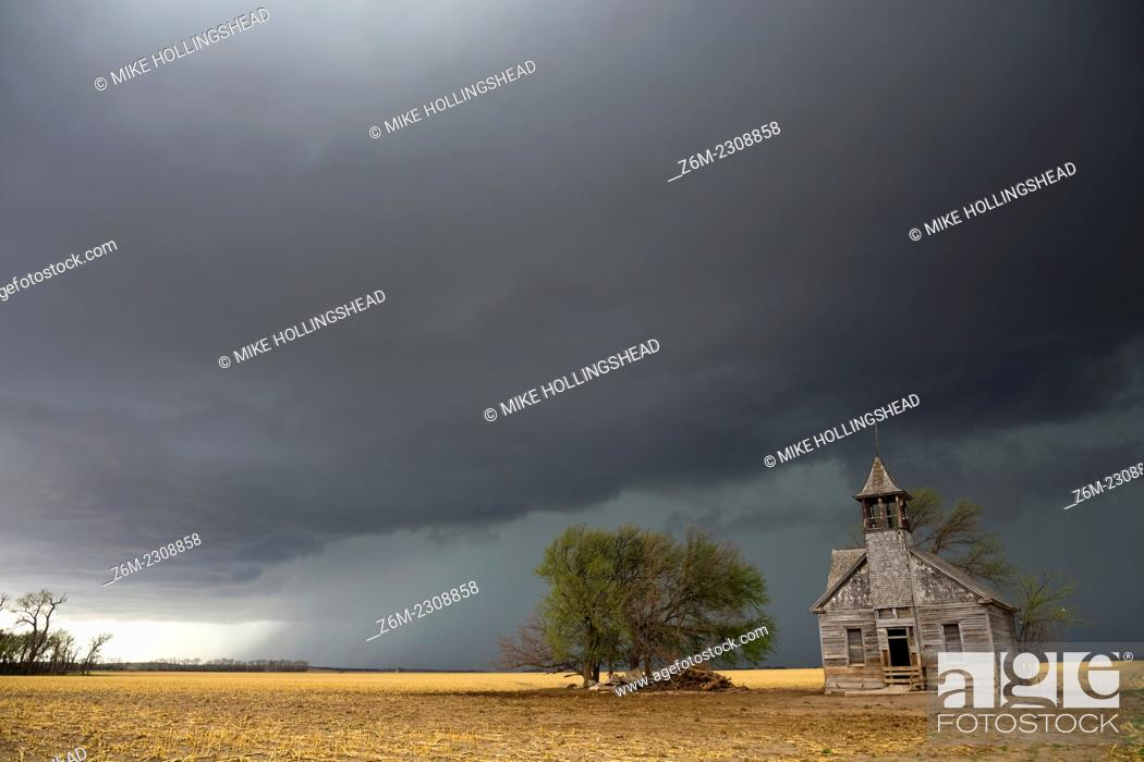 Stock Photo: Outflow behind a tornado warned supercell approaches an old weathered school house in eastern Nebraska.