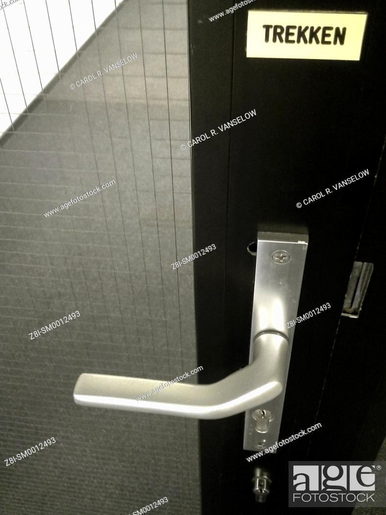 """Stock Photo: Glass and metal door. Sign above door handle says """"""""trekken"""""""" (pull)."""