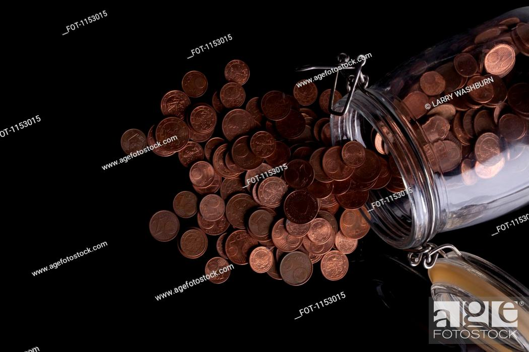 Stock Photo: A glass jar spilling copper Euro coins.