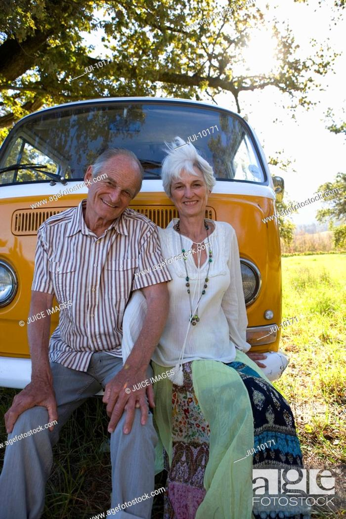 Stock Photo: Senior couple sitting in front of camper van, smiling, portrait.