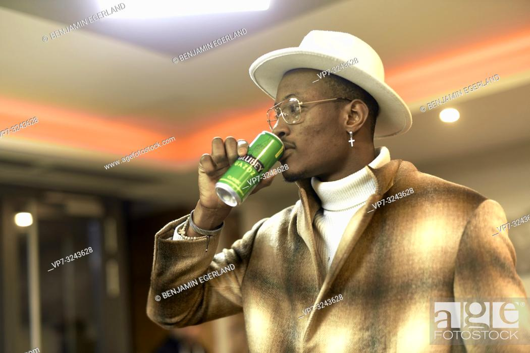 Stock Photo: stylish blogger man drinking energy drink indoors in bar, wearing men's fashion clothing outfit, side view upper body, Christian cross earring, in Munich.