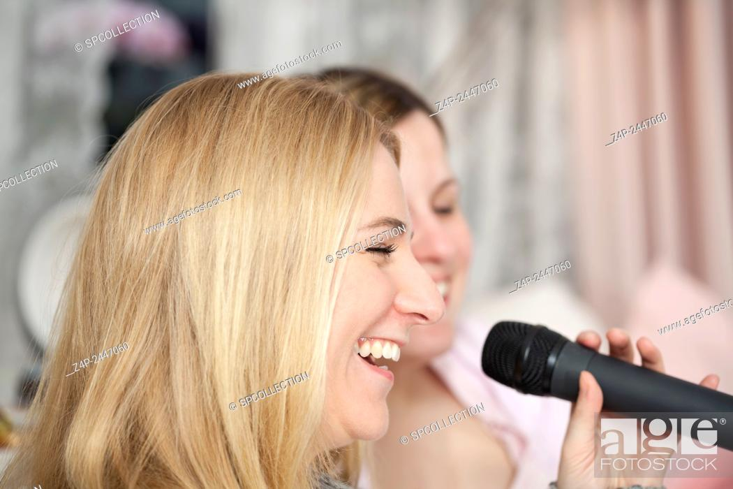 Stock Photo: Girlfriends singing karaoke.