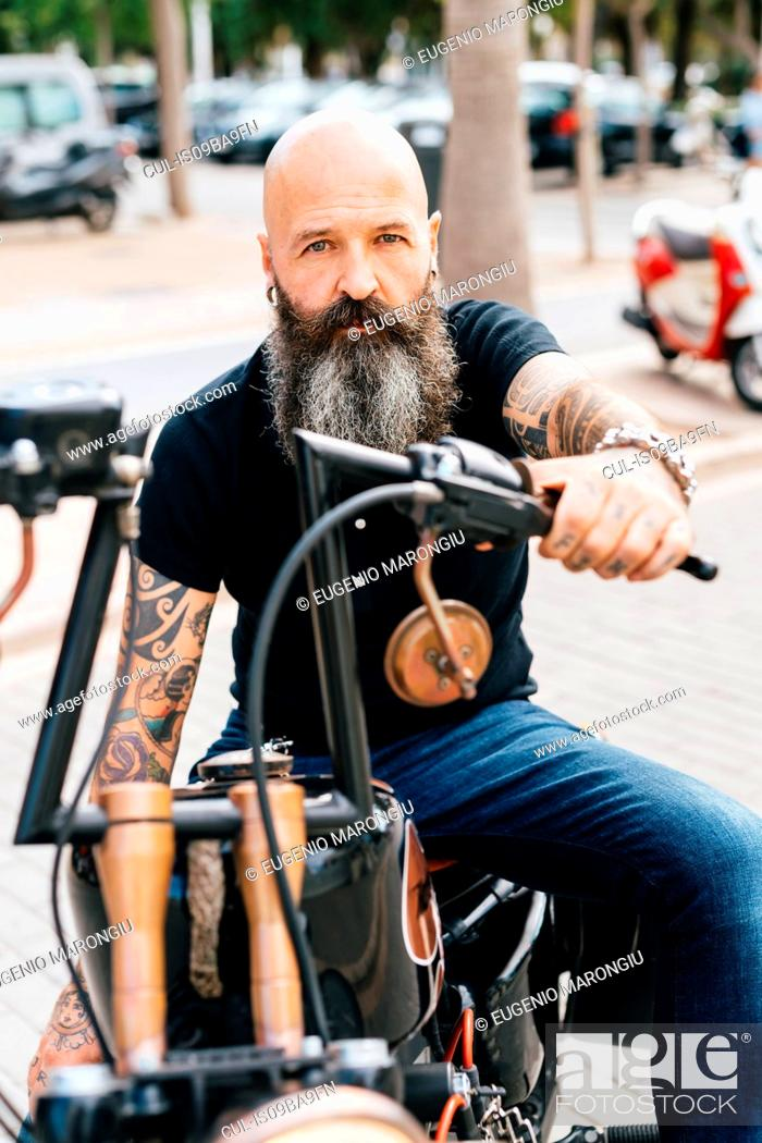 Stock Photo: Portrait of mature male hipster astride motorcycle in parking lot.