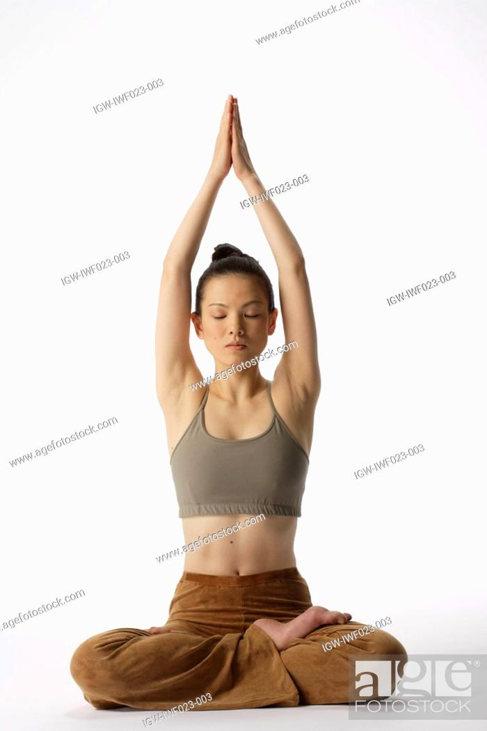 Stock Photo: Front view of a young woman meditating in lotus position.