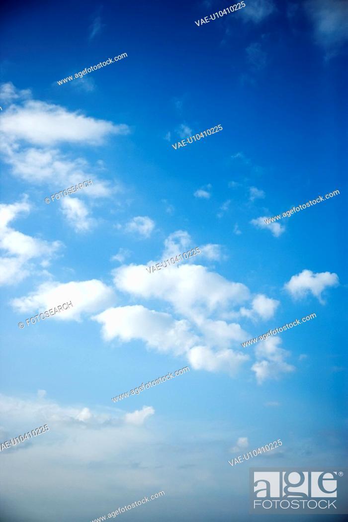 Stock Photo: Fluffy cumulus clouds in blue sky.