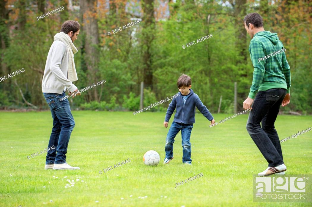Stock Photo: Boy playing soccer with two men in a park.