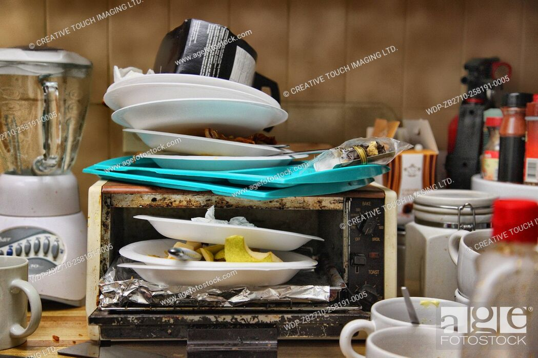 Imagen: Styrofoam plates with old food piled in and on a toaster oven on a messy kitchen countertop.
