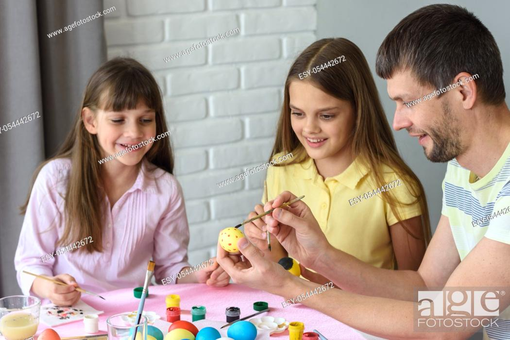 Stock Photo: Dad shows children how to easily and easily paint Easter eggs.