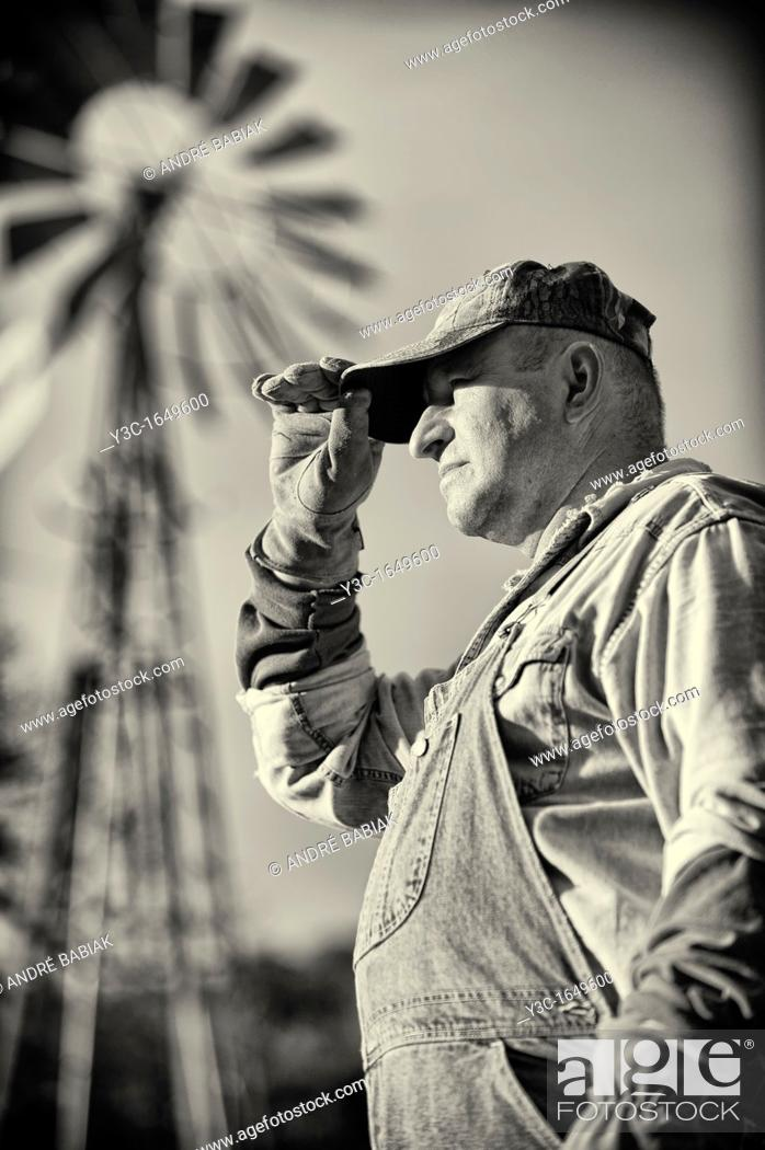 Stock Photo: Portrait of American Farmer Vintage Style Black and White with Ranch Windmill in Background.