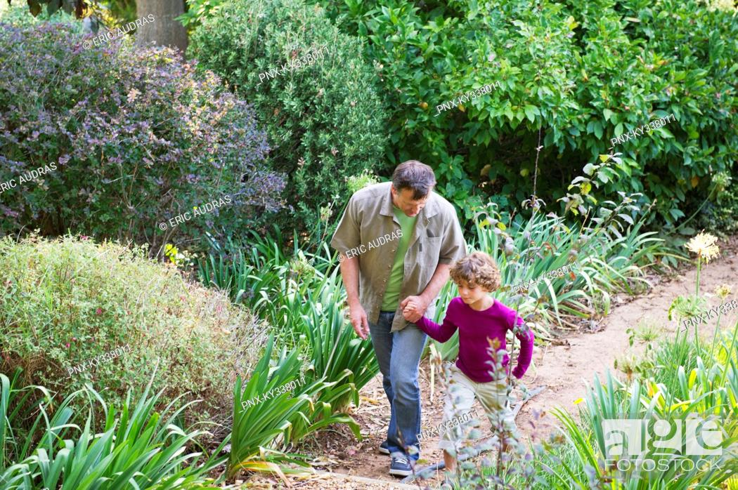 Stock Photo: Father and son walking in a garden.