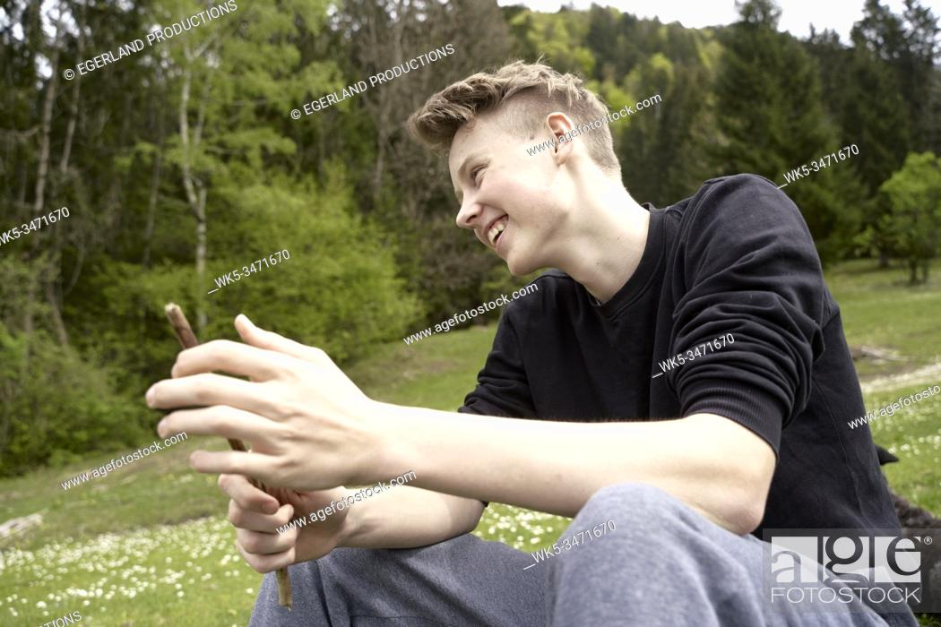 Imagen: Young boy in countryside, taking a rest. Bad Tölz, Upper bavaria, Germany.