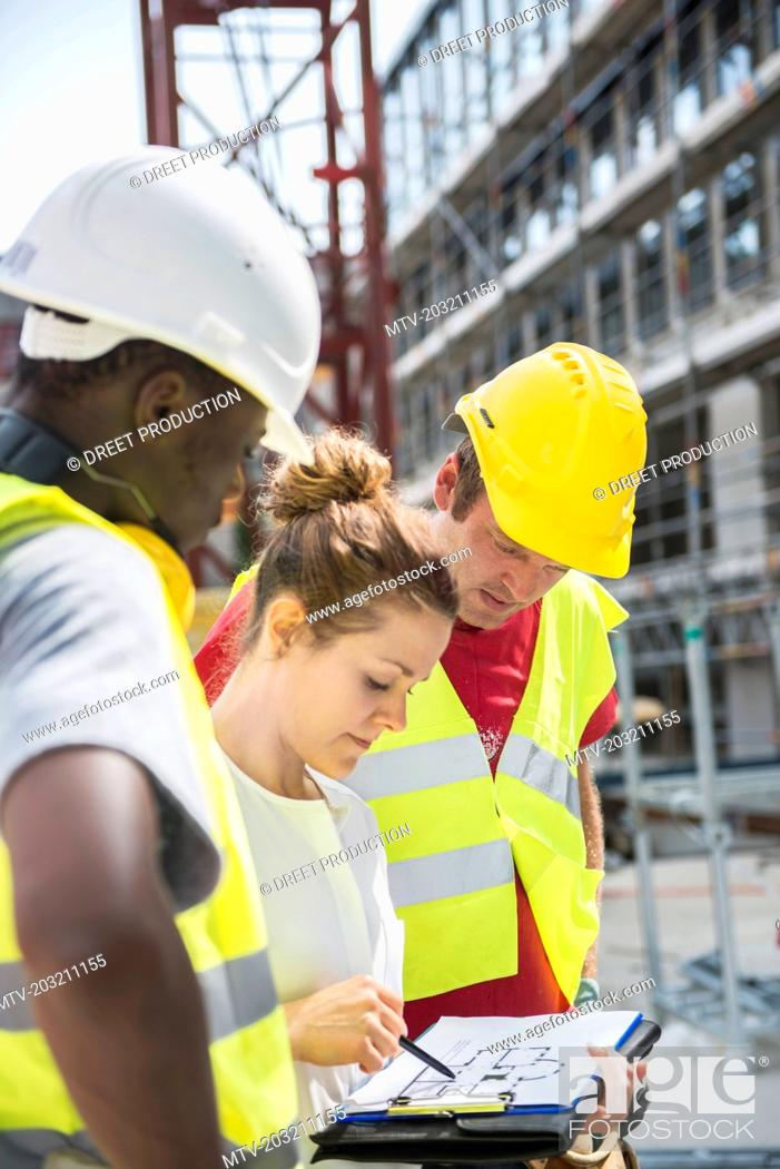 Stock Photo: Architect reviewing blueprint with construction workers at building site.