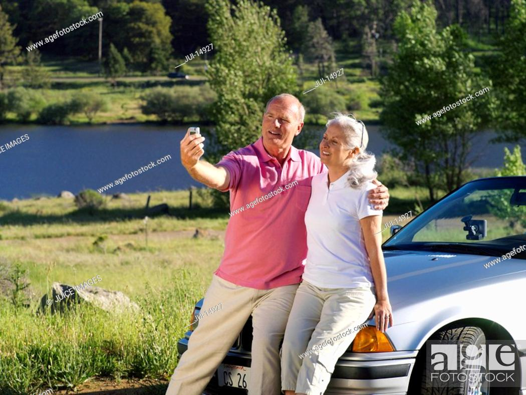 Stock Photo: Couple on bonnet of car taking photograph of themselves by river.