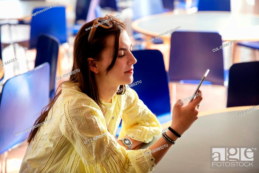 Stock Photo: Teenage girl reading text message on cellphone in school.
