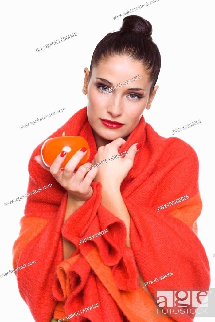 Stock Photo: Young woman wrapped in blanket, holding candle.