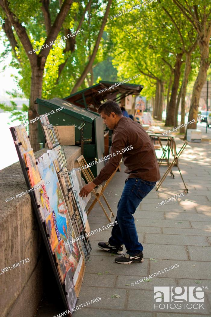 Imagen: Traditional books and gifts seller (bouquiniste) organizing the display of his products next to the banks of the Seine. Paris, France.