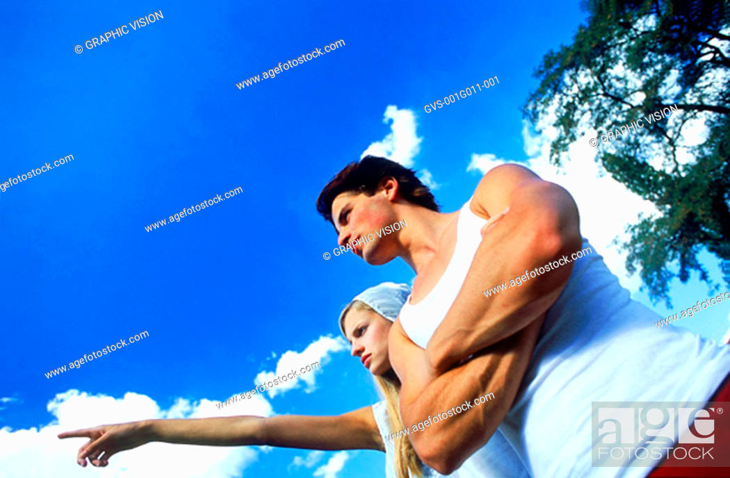 Stock Photo: Young woman standing with man pointing.