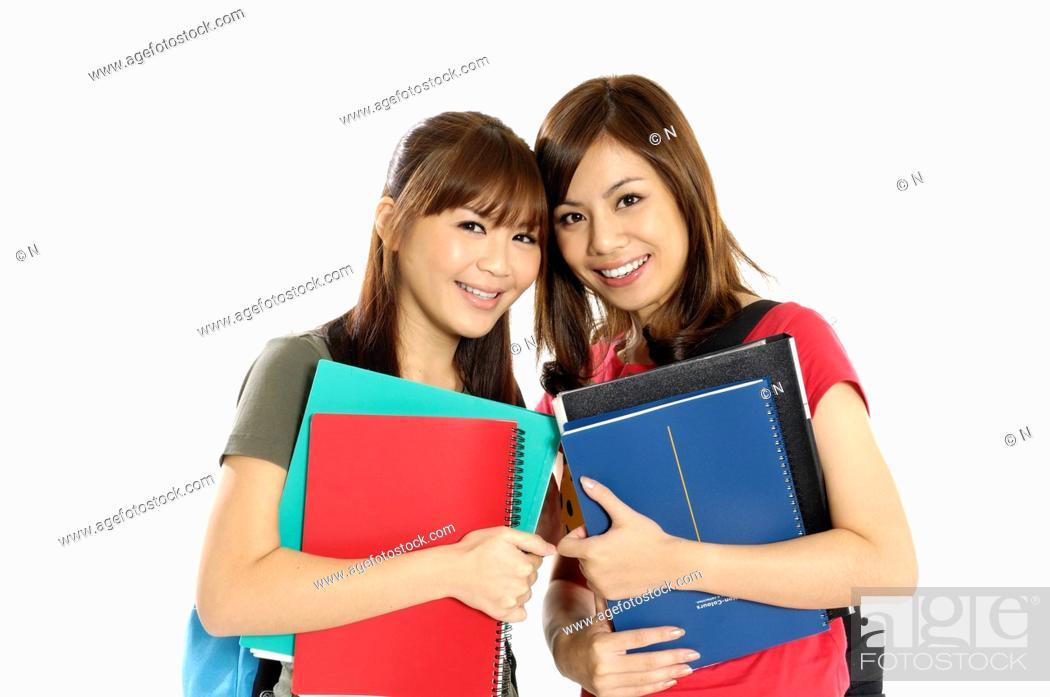 Stock Photo: Female university students holding books.