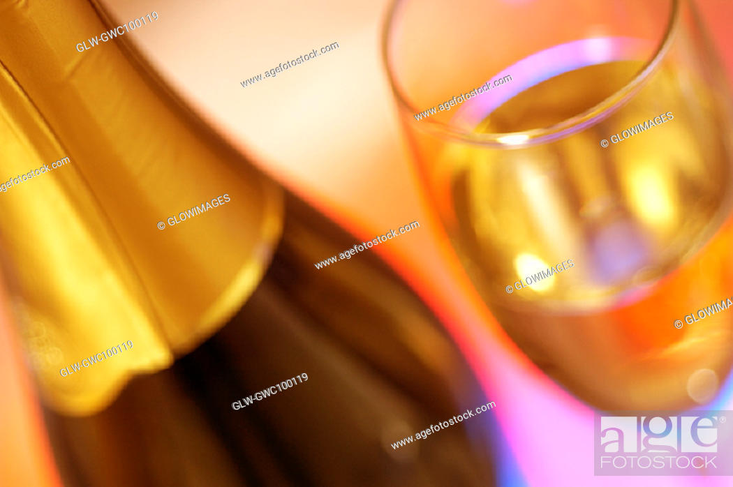 Stock Photo: Close-up of a champagne bottle with champagne in a champagne flute.