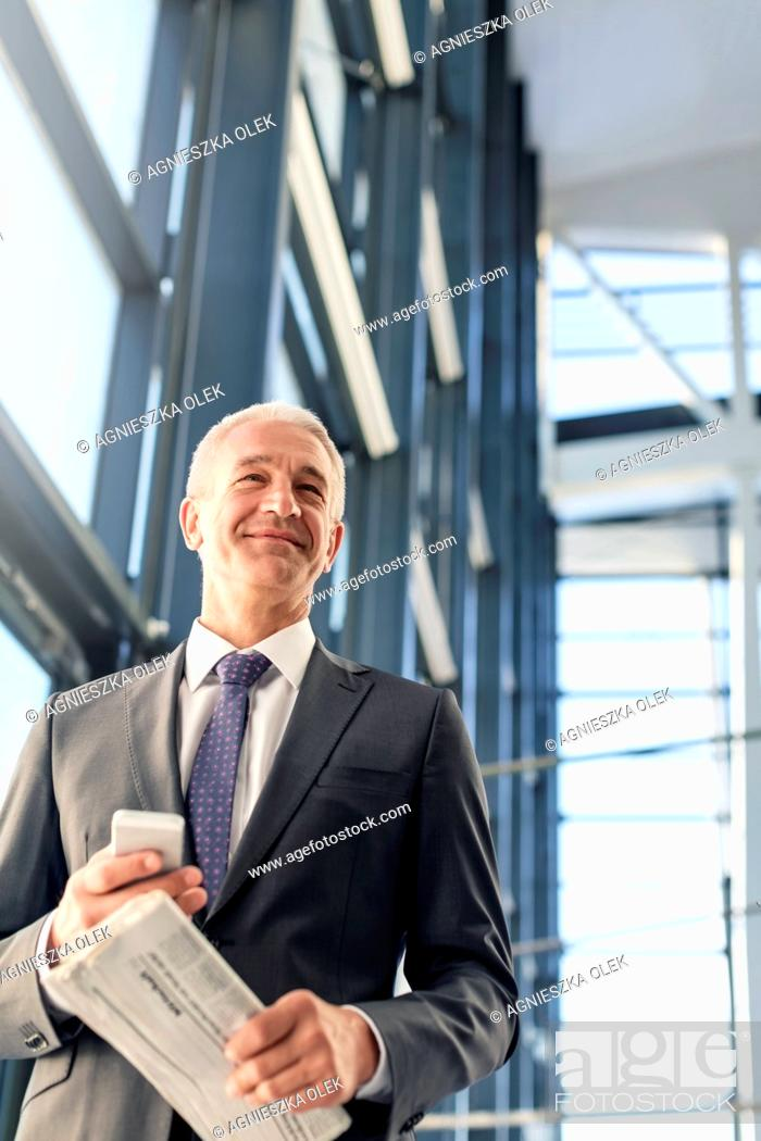 Stock Photo: Smiling businessman with cell phone and newspaper in airport.