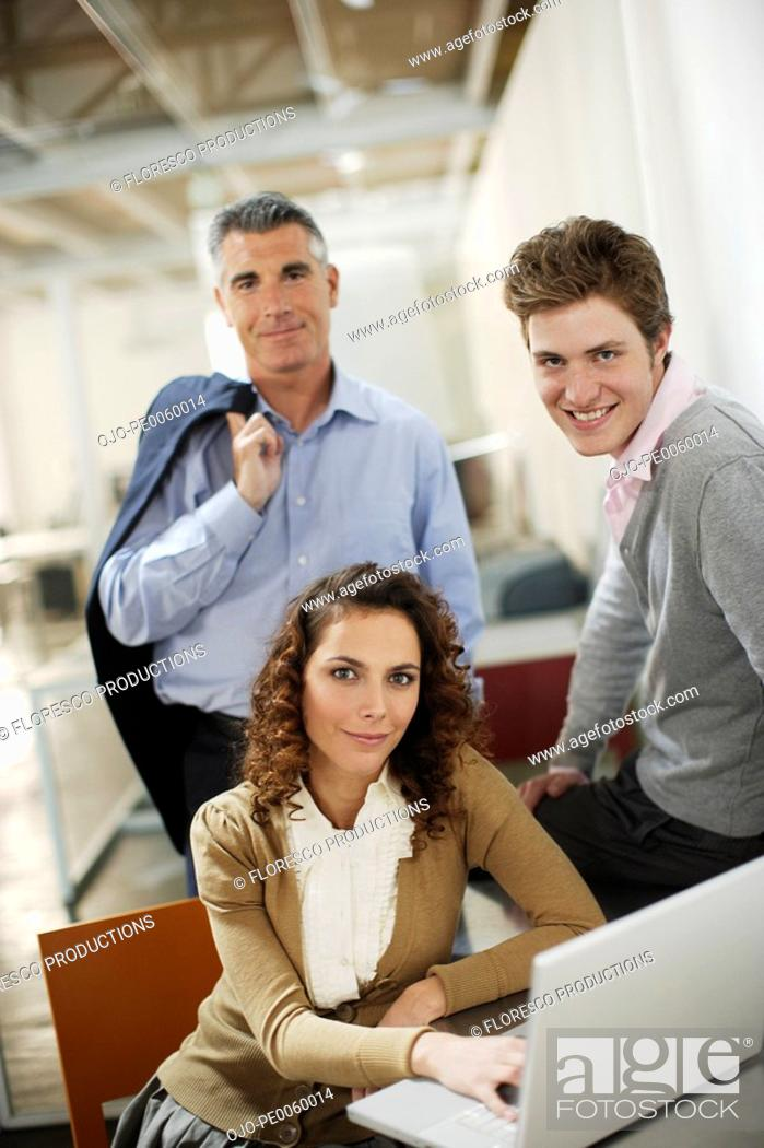Stock Photo: Three businesspeople in office with laptop.