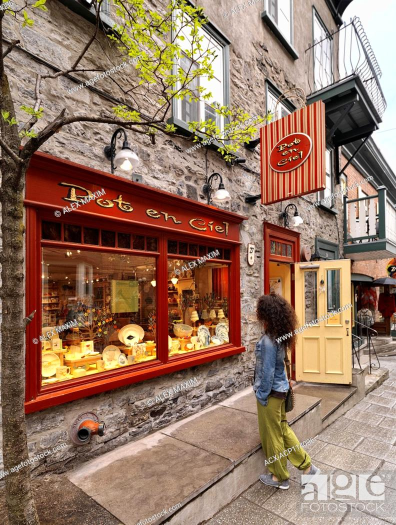 Stock Photo: A young woman standing in front of Pot en Ciel store on Rue Petit Champlain historic street in Old Quebec City and looking at its colorful display window.