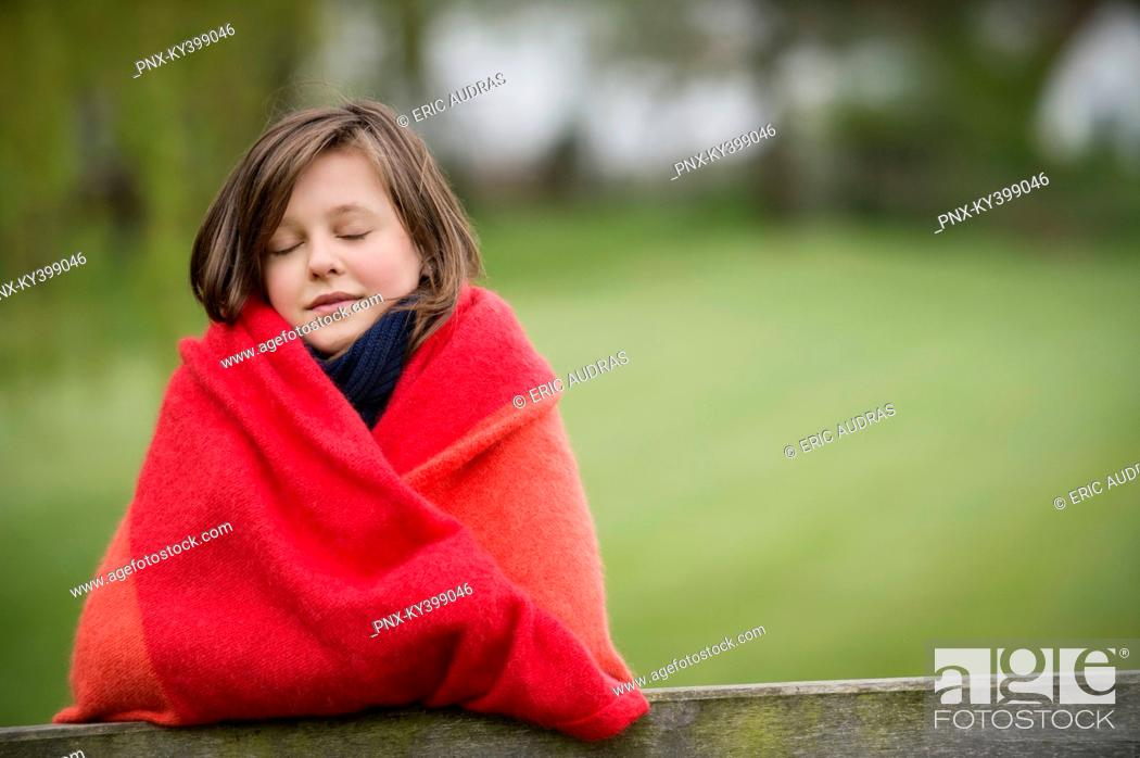 Stock Photo: Girl wrapped in a blanket with her eyes closed in a farm.