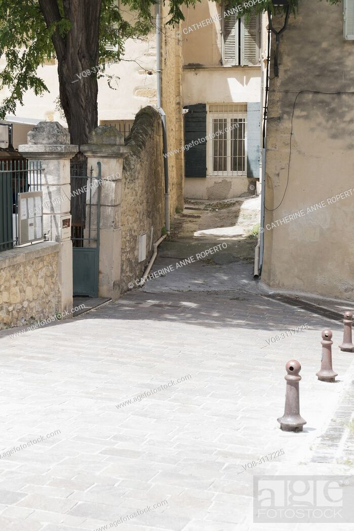 Stock Photo: Bright, dappled sunlight in the old quarter of Salon, Provence, with traditional teal coloured wooden shutters and shady foliage, France.