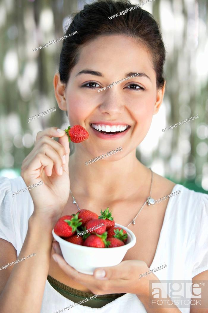 Stock Photo: Portrait of a young woman holding a bowl of strawberries.