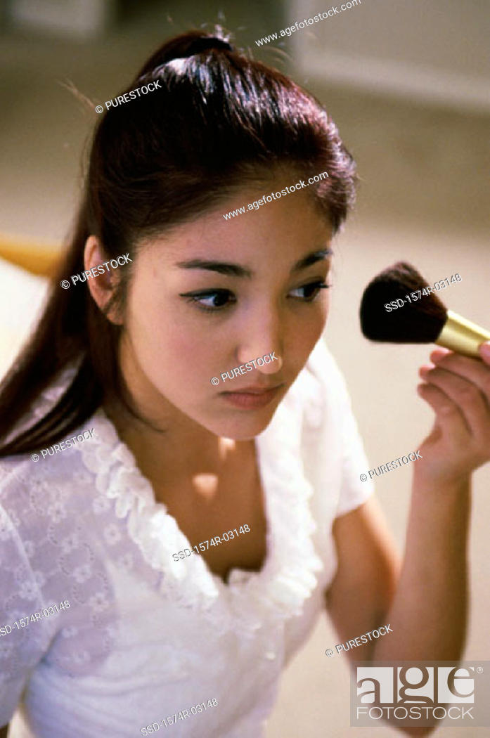 Stock Photo: Young woman applying make-up with a brush.